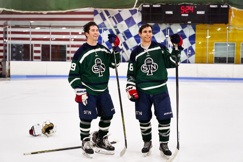 Adam Kaiser, left, and Matt Cook wearing jerseys with the crest of the St. Nicholas Hockey Club.